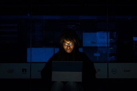 A woman learns in the dark room on her laptop
