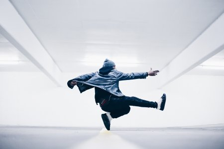 A dancer jumps into the air in a brightly lit hall