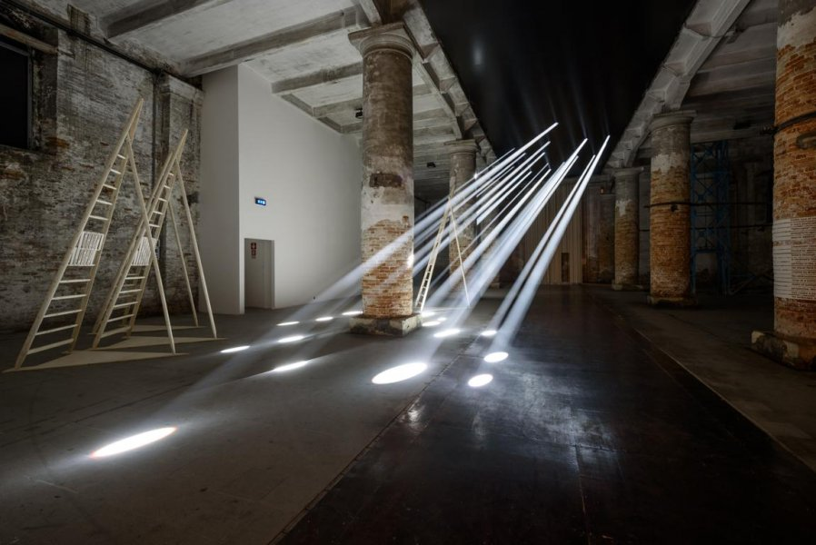 Rays of light hit the ground of a hall in which a ladder is standing